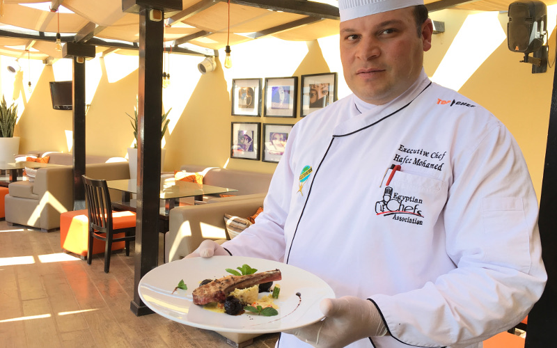 A chef is serving a plate of lamp chops and couscous in El Gouna Hotels Red Sea