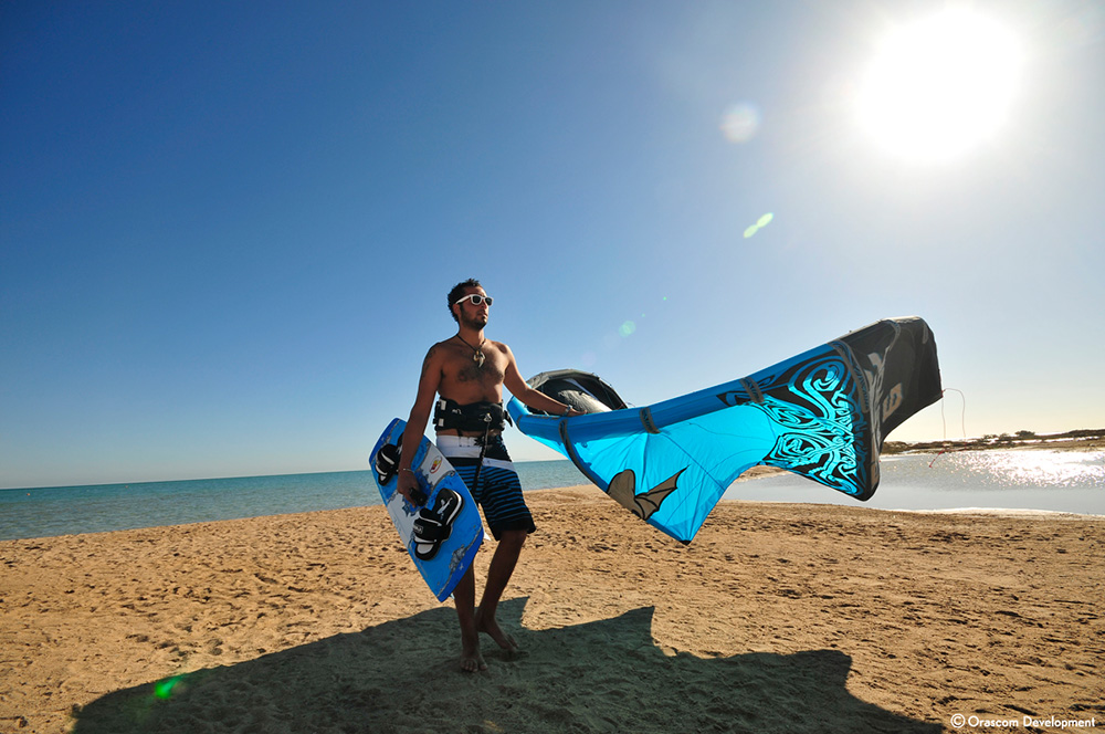 A kite surfer is holding his kite and bar on the shores of El Gouna Red Sea
