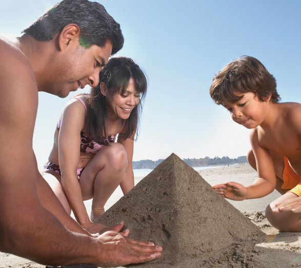 Family building sandcastle at beach in The Three Corners hotels El Gouna