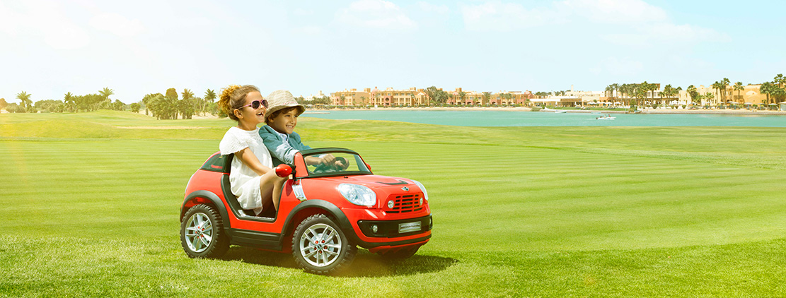 Two kids riding a baby car at Steigenberger Golf Resort in El Gouna Red Sea