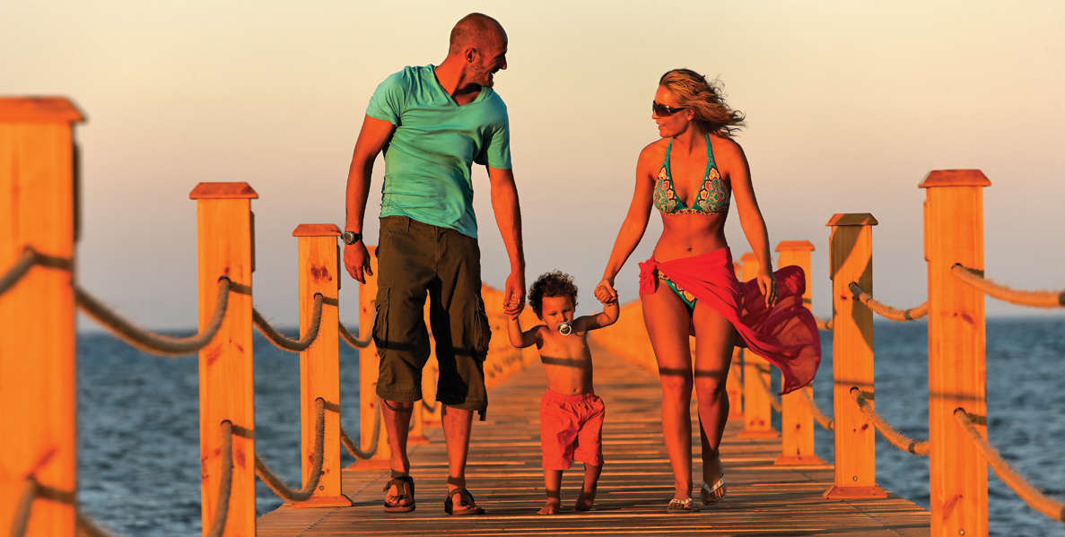 Two parents are holding their baby hands and walking over a jetty during sunset at Bellevue Hotel El Gouna