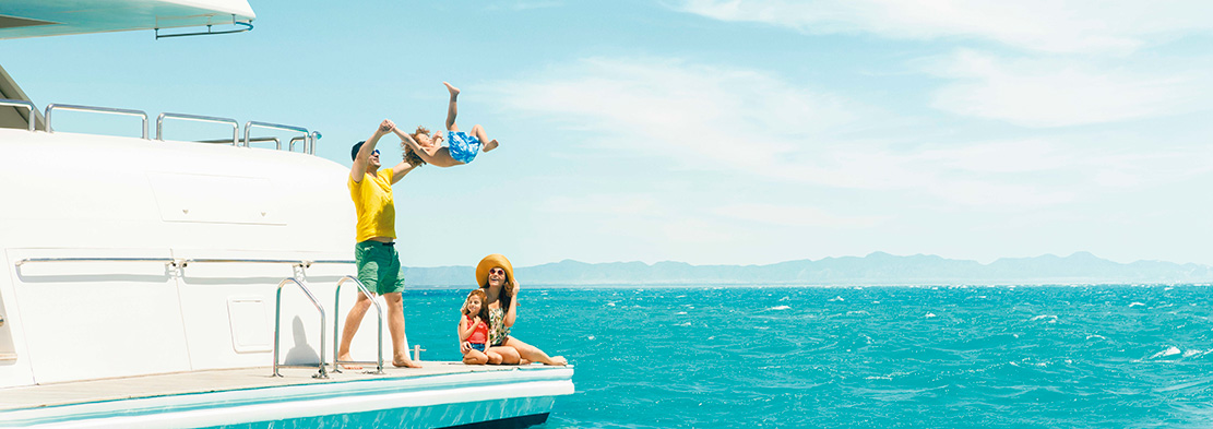 A father is swinging his baby in a sea trip over Red Sea in El Gouna