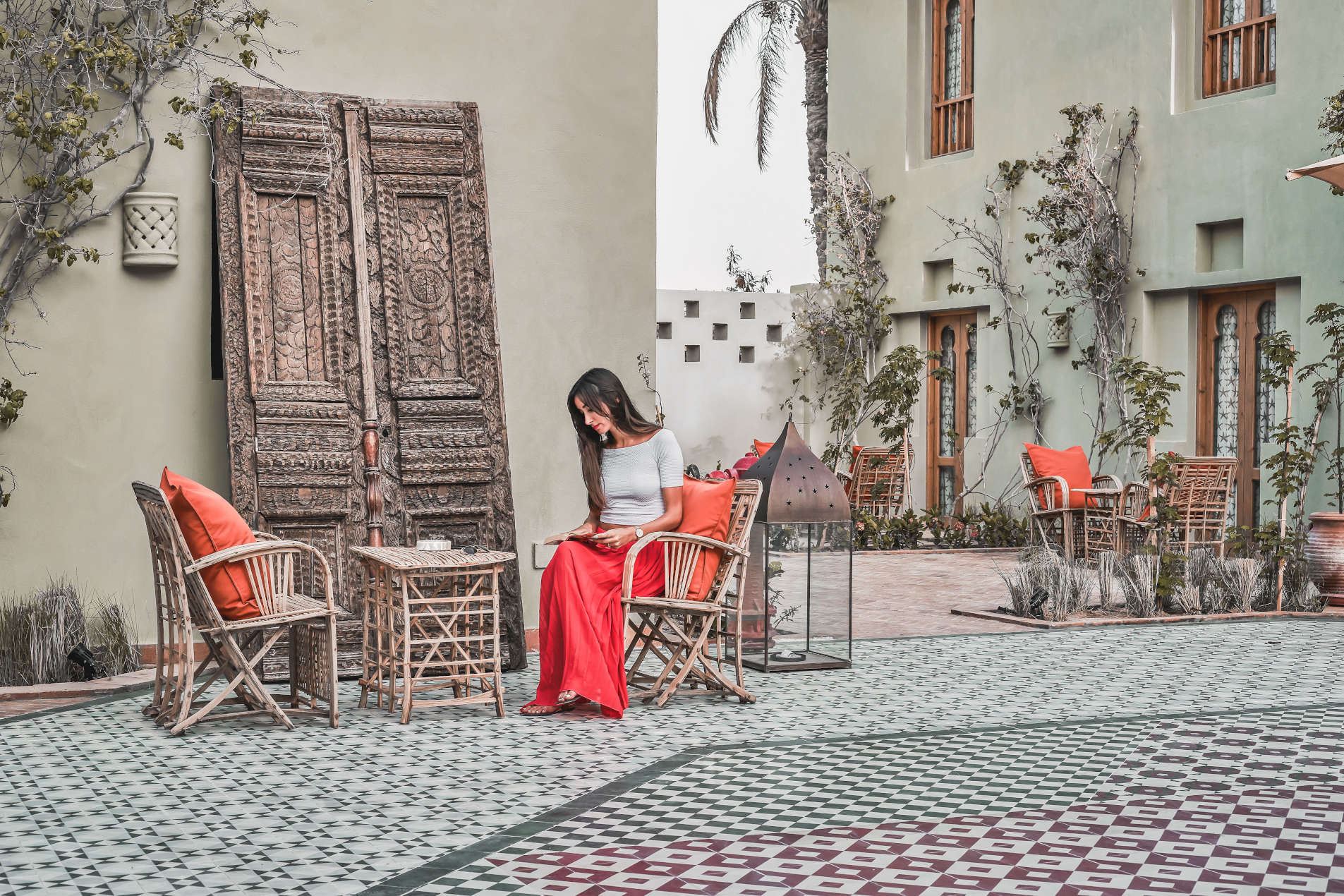 Picturesque Courtyard of Ali Pasha hotel where a female guest is sitting and reading, all reflecting the unmatched lifestyle of Ali Pasha hotel El Gouna