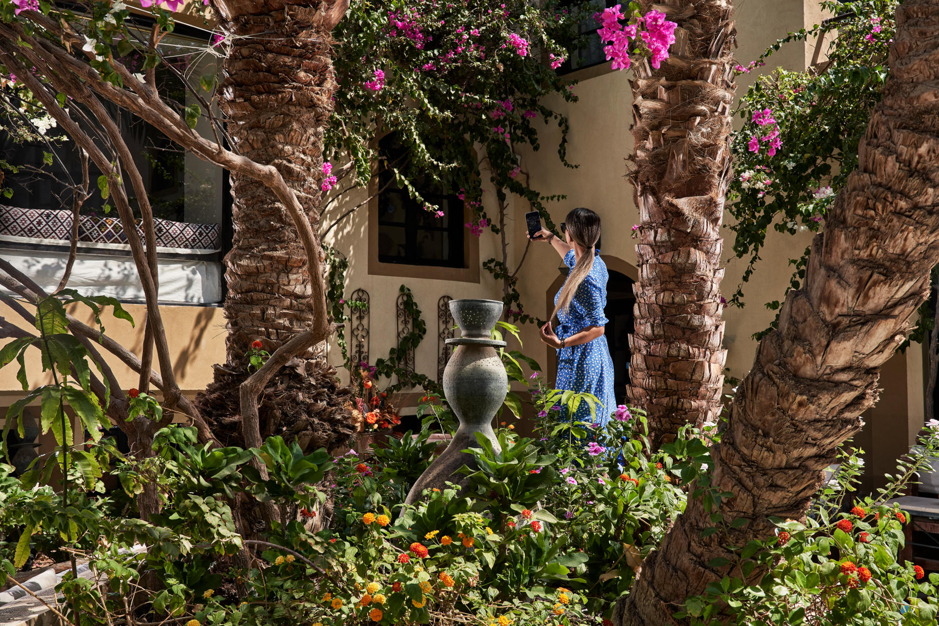 A female guest of Dawar El Omda Boutique Hotel talking a selfie in the hotel's courtyard filled with picturesque greenery