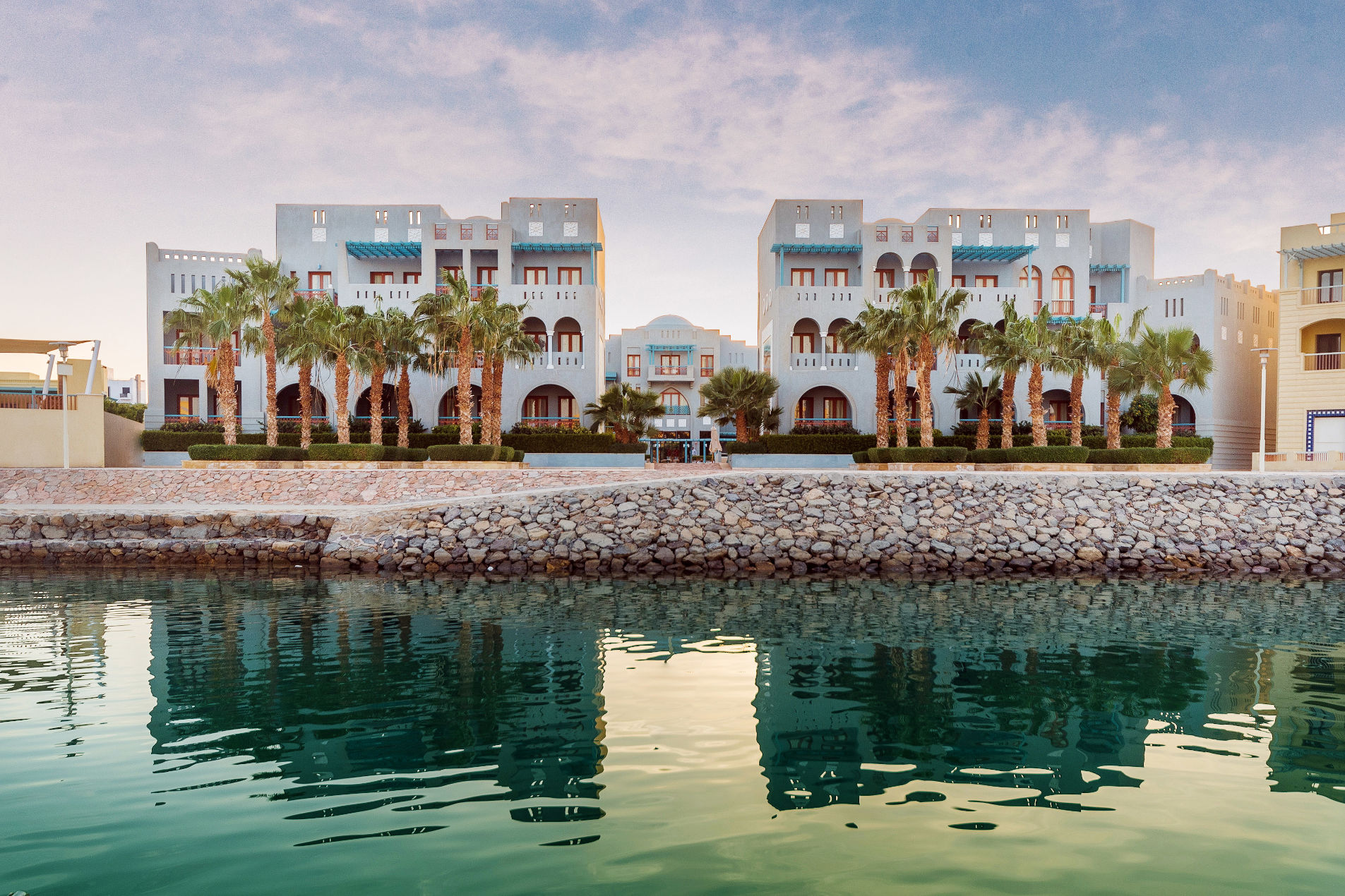 Overview of Fanadir Marina Hotel in El Gouna with a palette of blue and wooden brown from Abu Tig Marina Side