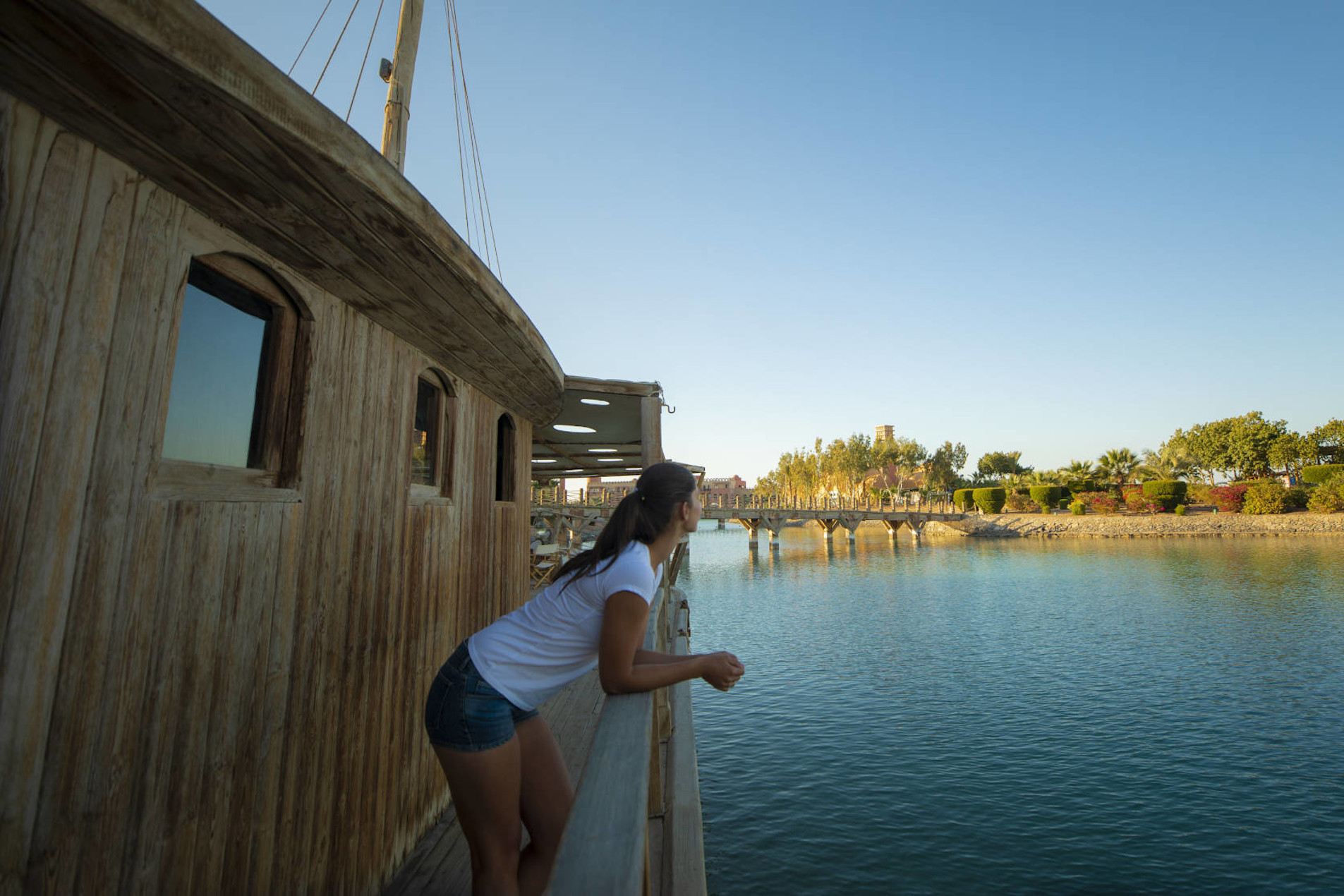 A girl is standing on the wine boat with the view of Red Sea waters in Sheraton Miramar Resort El Gouna