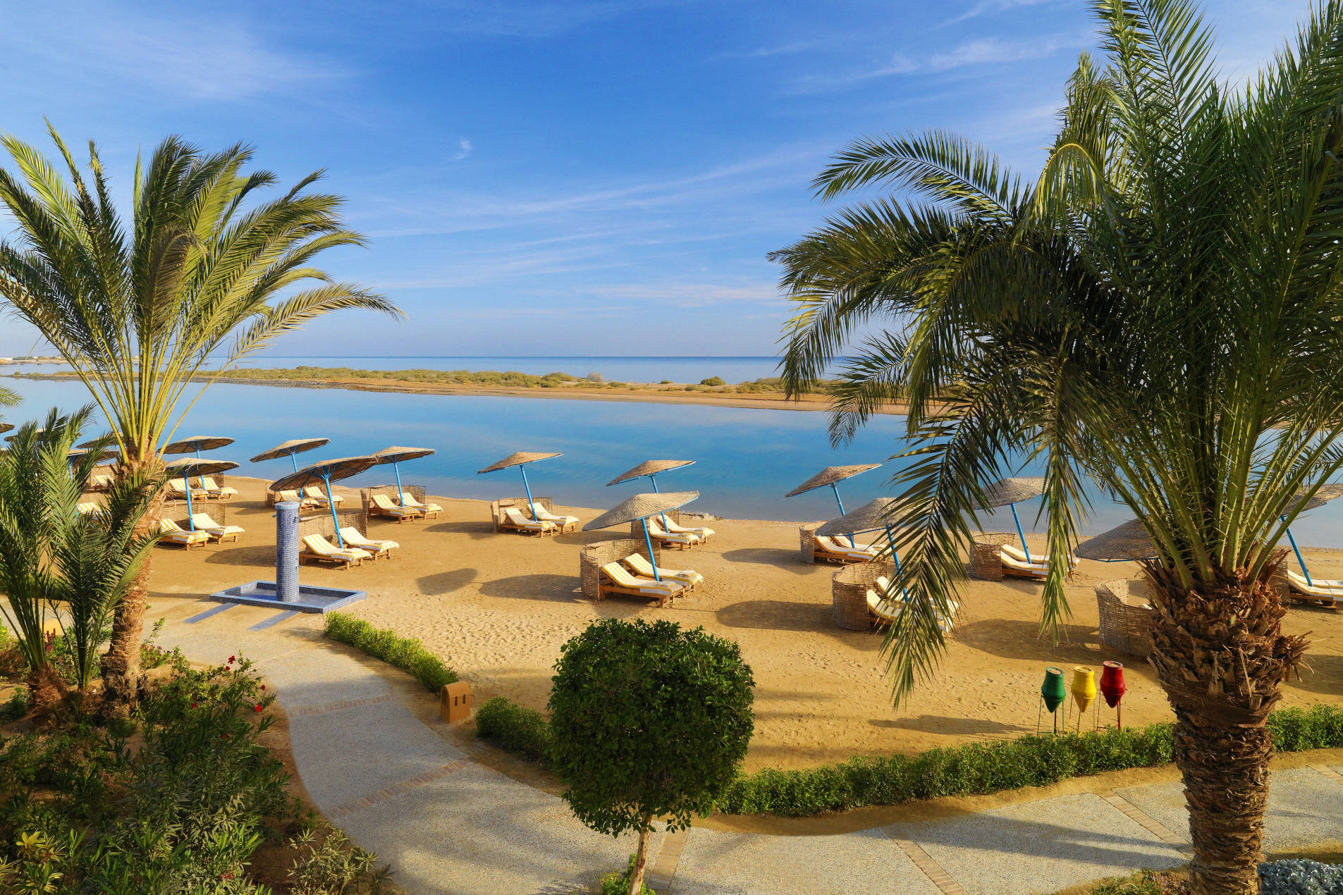 A beach view of Sheraton Miramar El Gouna with laidback sunbeds and the blue water of Red Sea