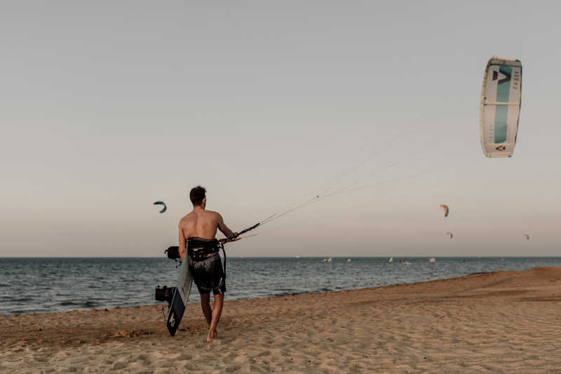 a kiter walking by the beach at kite center space at casa cook el gouna hotel
