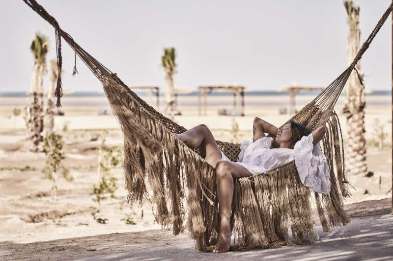 a girl on a hammock by the beach at casa cook el gouna hotel