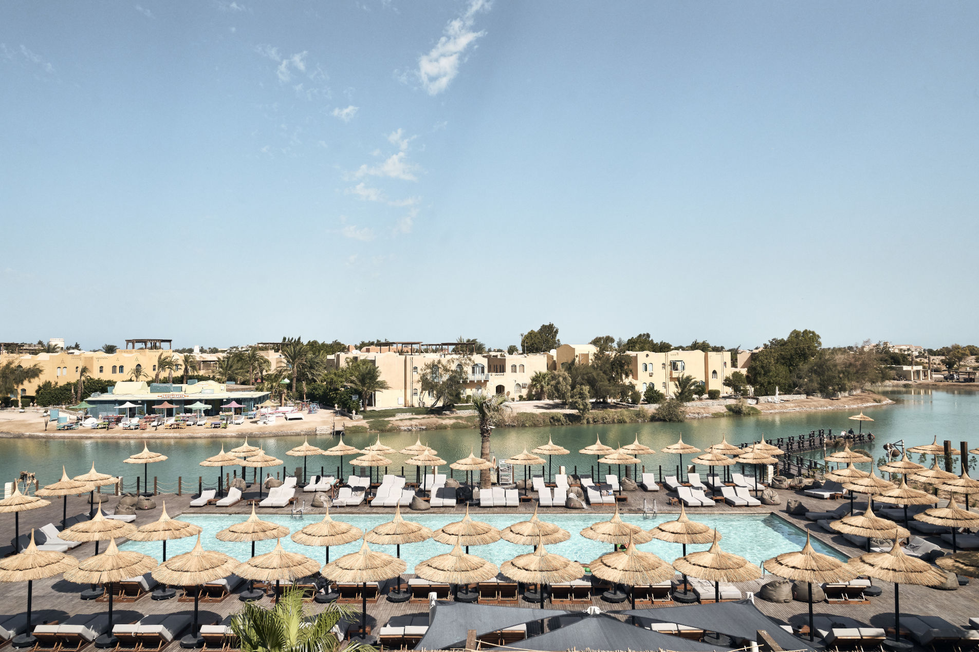 An overview of adults swimming pool at Cook's Club Hotel surrounded by laidback sunbeds with a view to Red Sea lagoon