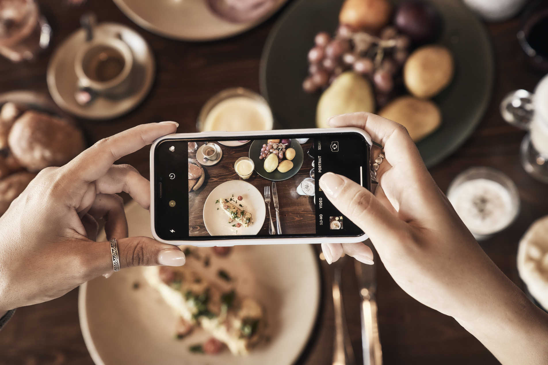 A girl capturing dining at Cook's Club Cantina Restaurant with her Mobile Phone in El Gouna Hotels