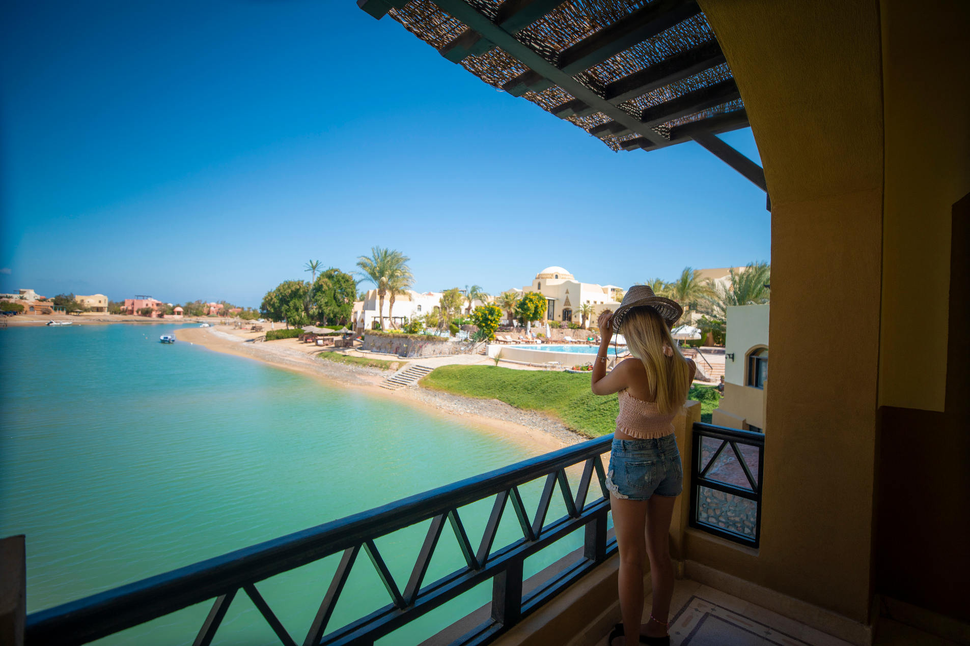 A female Guest standing in the terrace of Dawar El Omda Hotel room overseeing picturesque lagoon, Greenery & Infinity Pool