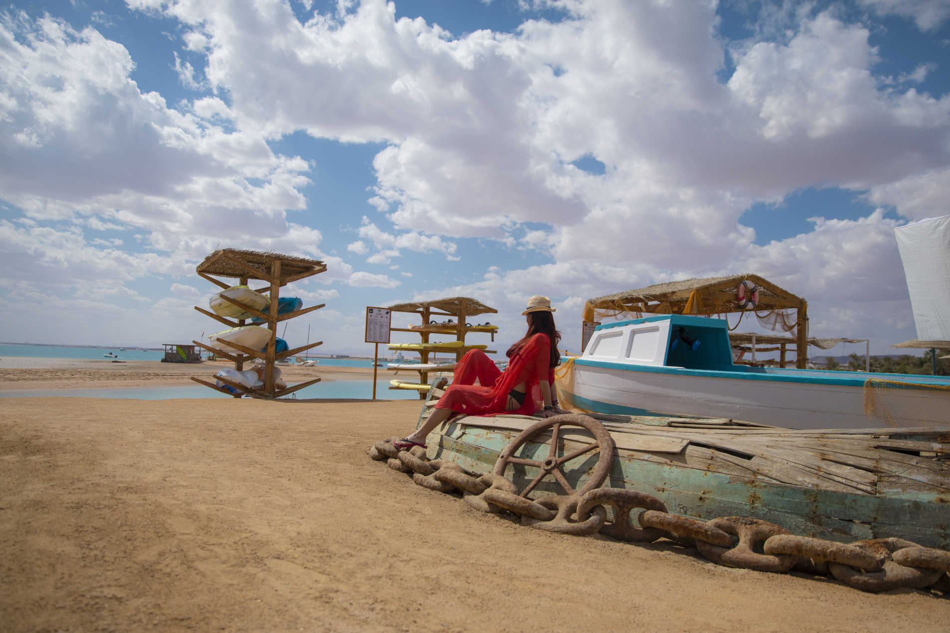A girl is sitting on a vintage boat at Club Paradisio Sandy Beach and the sky is full of clouds in El Gouna 4 Stars Hotel