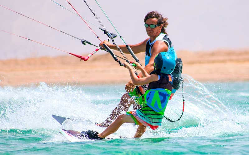 A kitesurfer with a kid kitesurfing in Red Sea in El Gouna