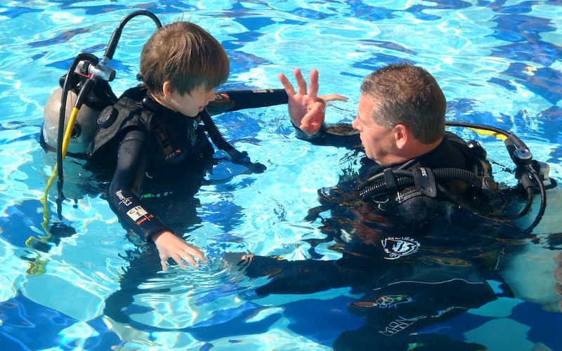A diving coach in El Gouna giving a guide to a kid in a hotel pool