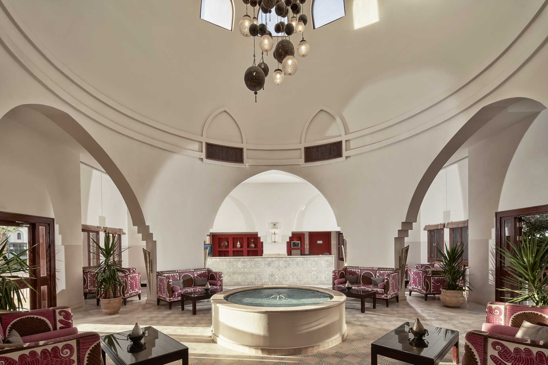 Mosaique Hotel Lobby in Moroccan style mixed with brown pink sofas, high ceiling and centered fountain in El Gouna