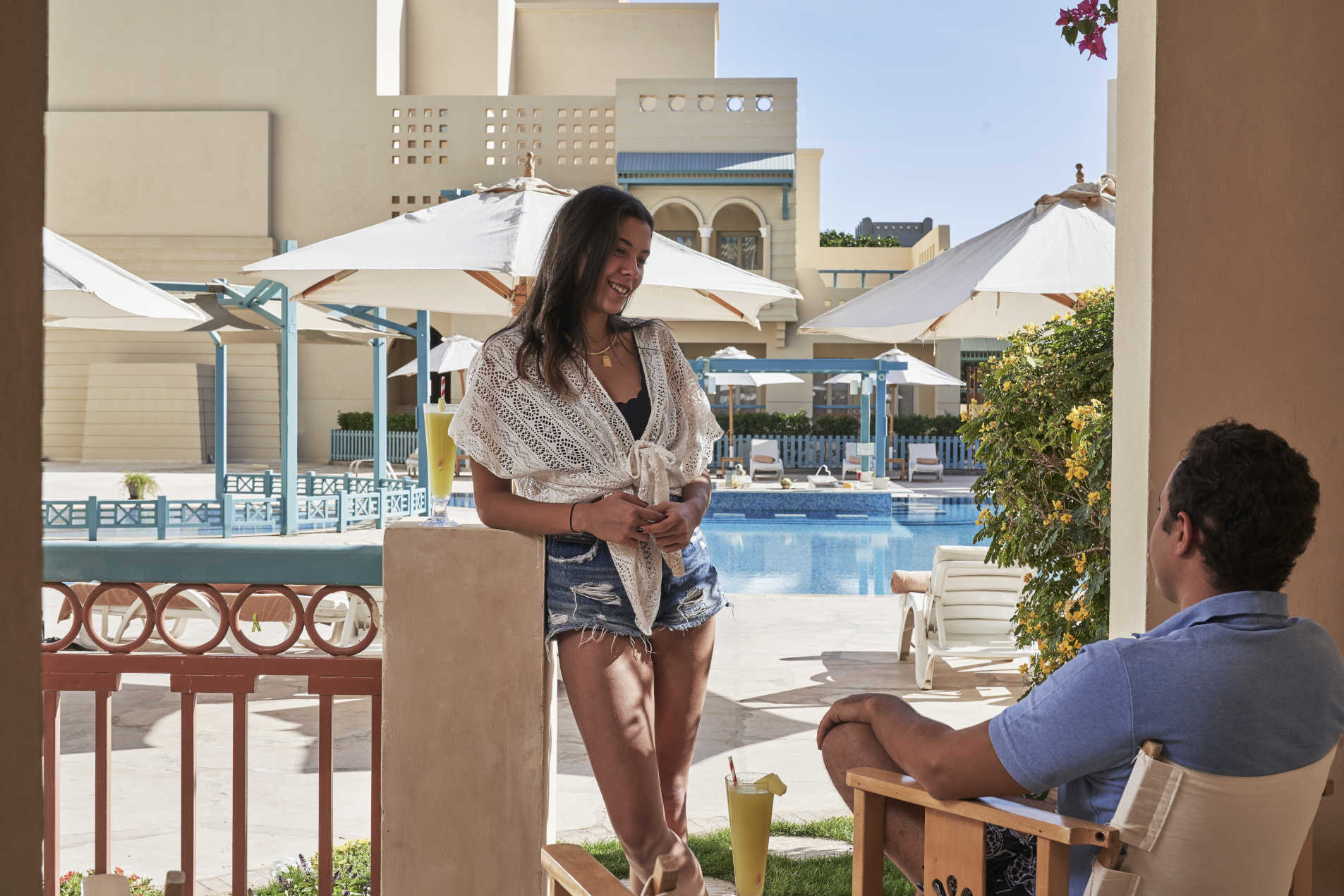 A lady and a man enjoying their drink in the terrace of Mosaique hotel room with a pool view in El Gouna