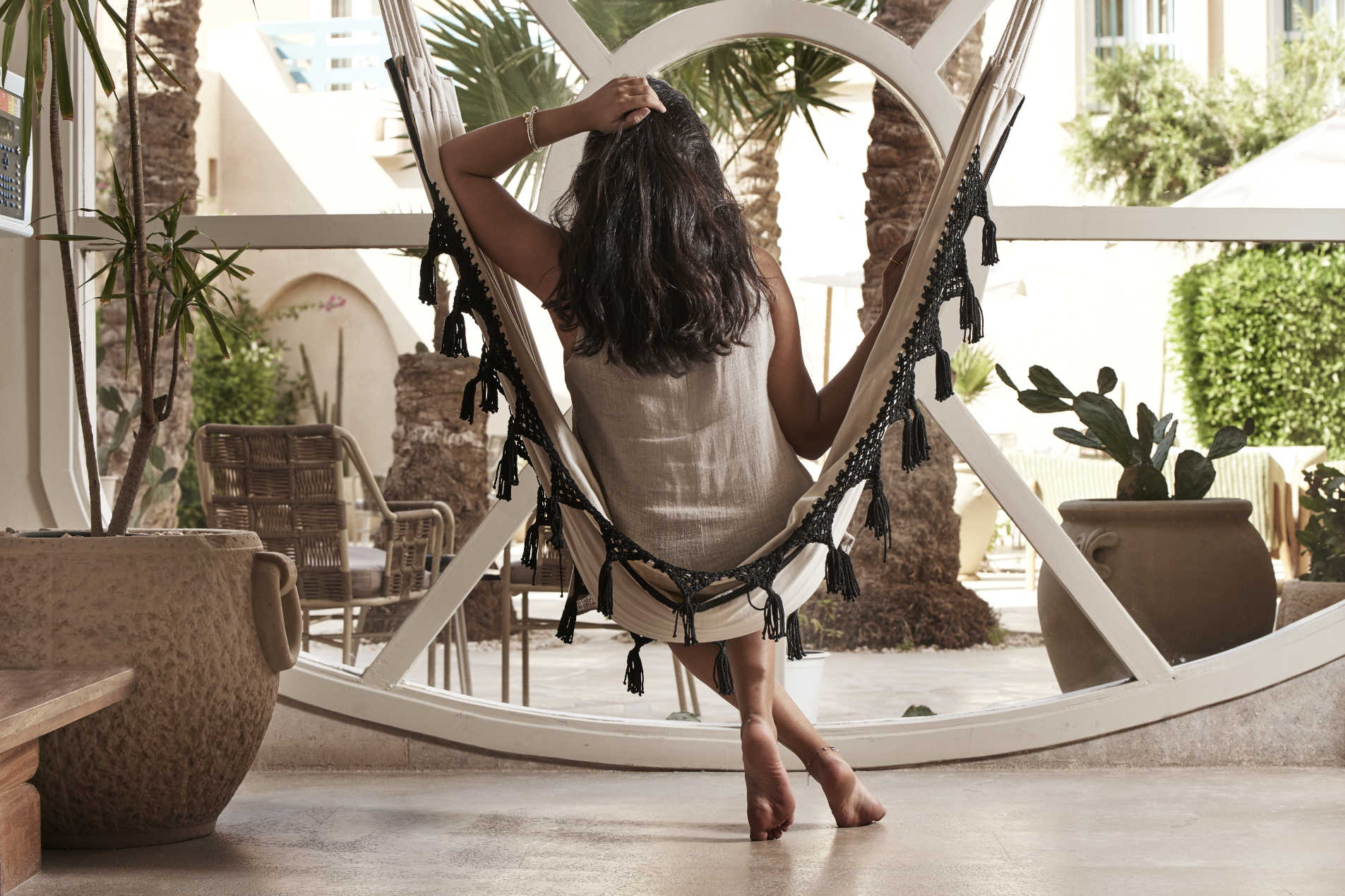A female guest relaxing on a hammock in the Captain's Inn El Gouna Hotel lobby while looking at the Hotel's courtyard plants