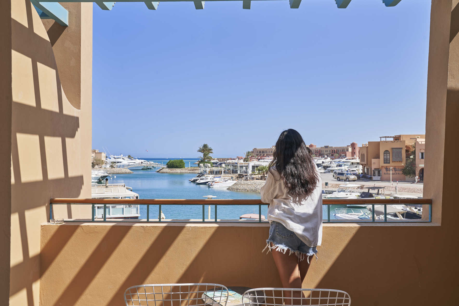 A female guest looking at the Abu Tig Marina & yachts spectacular View from Captain's Inn hotel El Gouna Egypt Room Terrace