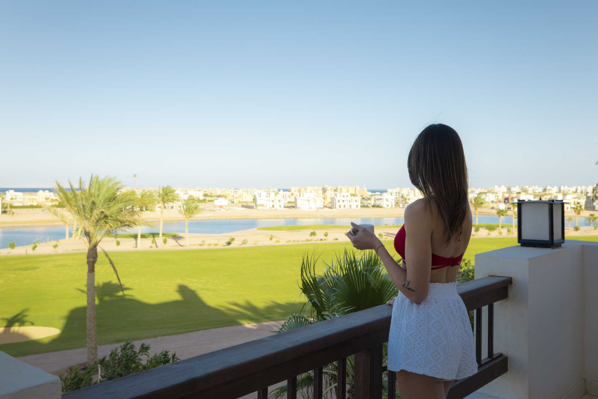 A girl is having her coffee in the room terrace with a view to greenish golf of Ancient Sands Resort in El Gouna Red Sea