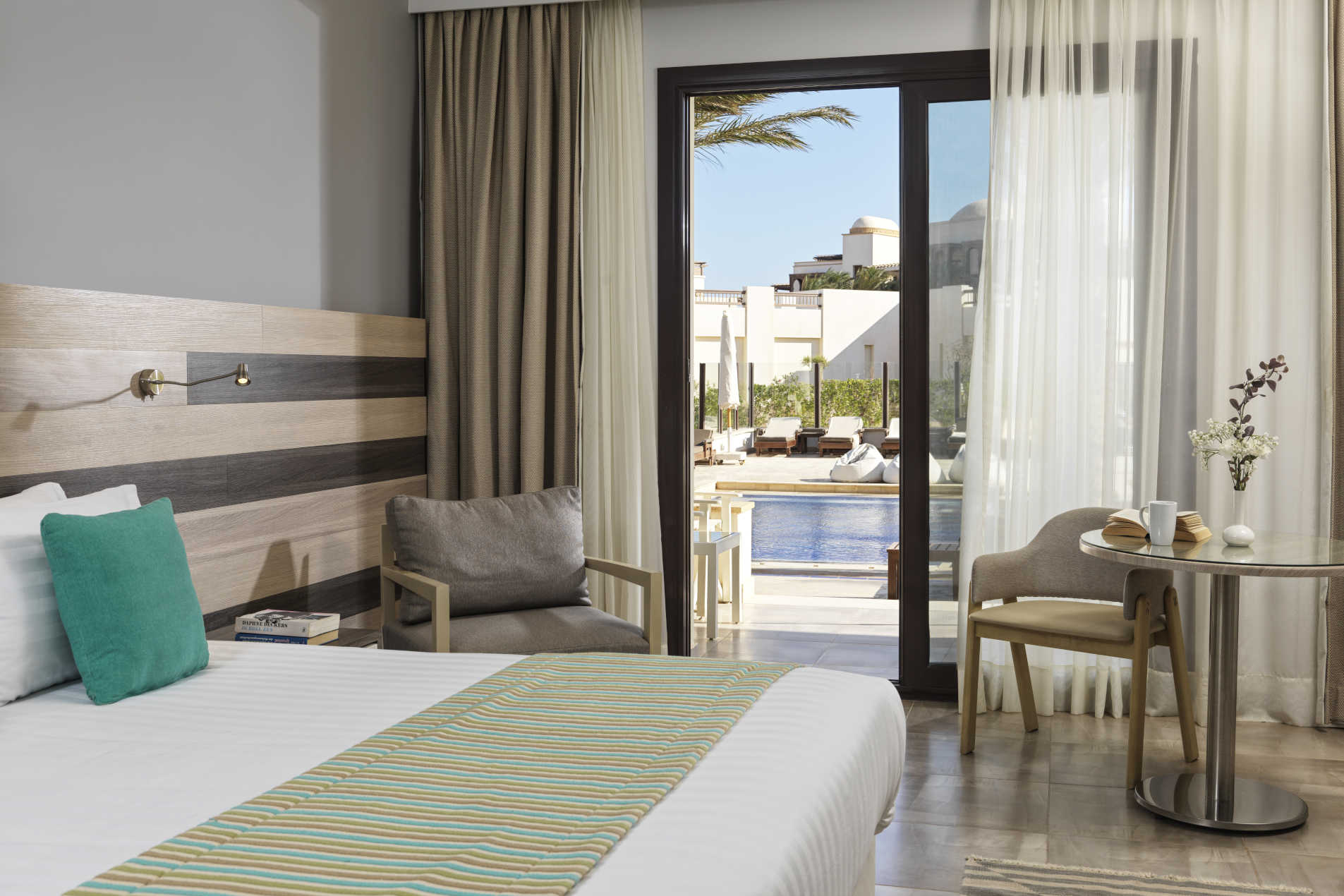 The king bedroom at Ancient Sands Resort in El Gouna with a glass door to the pool and an outdoor sitting area