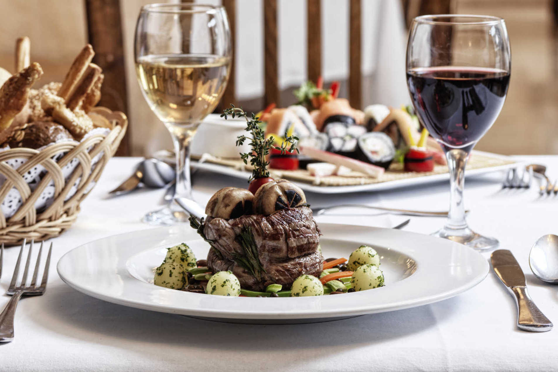The dining at Ancient Sands and a steak plate served with drinks and bakeries basket in El Gouna resort restaurant