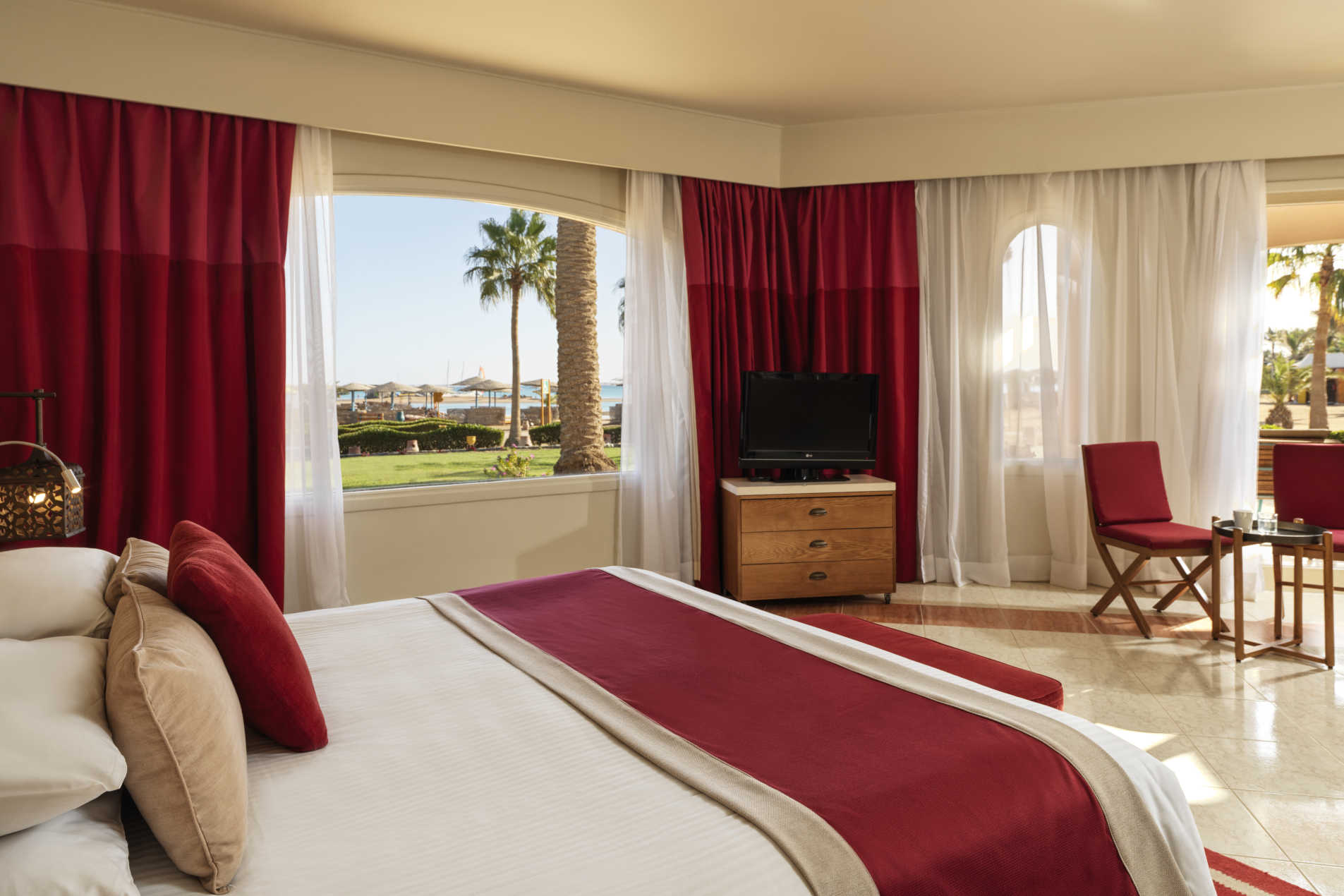 The kingbed of junior suite at Labranda Club Paradisio Hotel in El Gouna in a red theme and overlooking Red Sea waters and hotel gardens