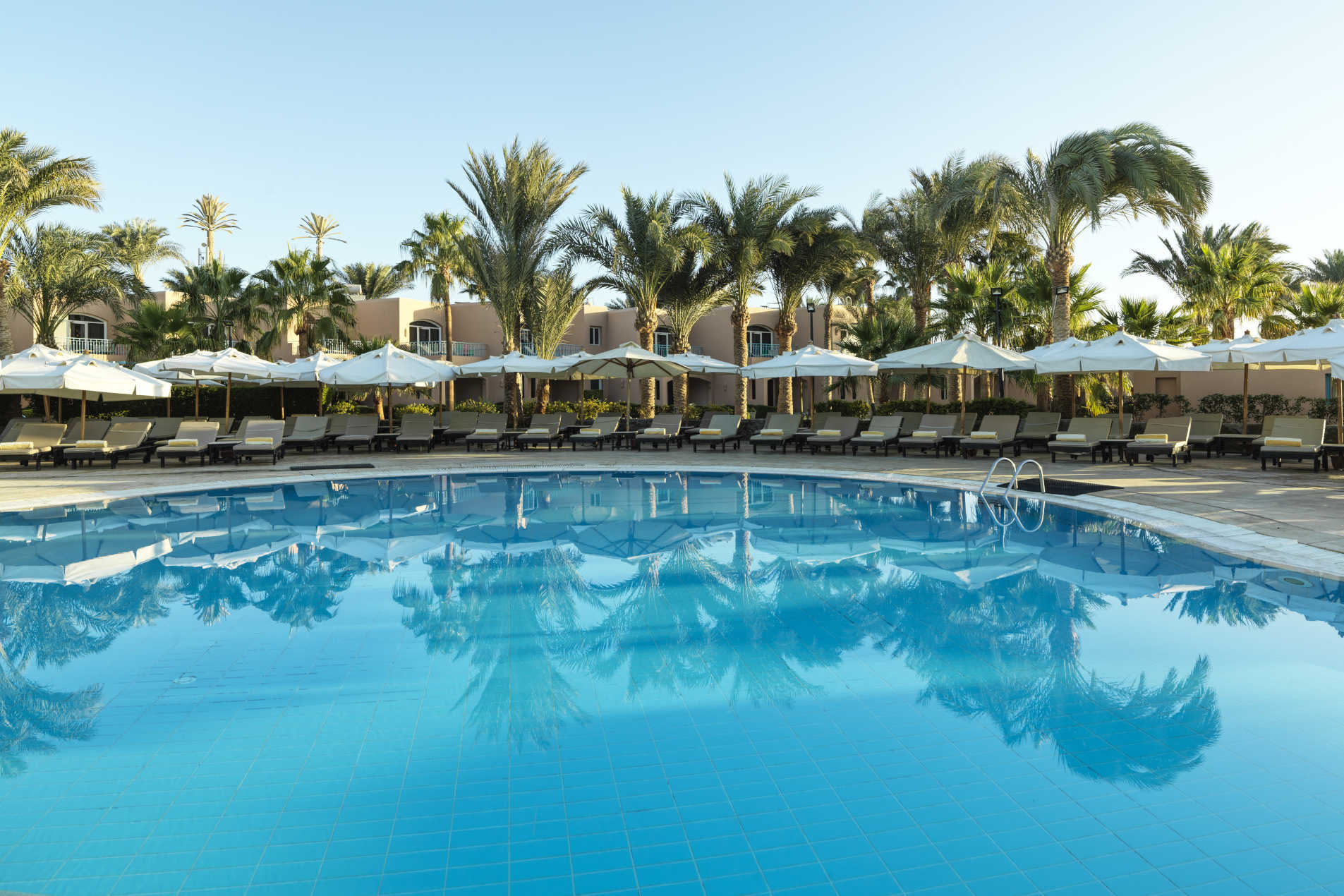 Swimming Pool of Labranda Club Paradisio Hotel in El Gouna surrounded with laid back sunbeds and umbrellas