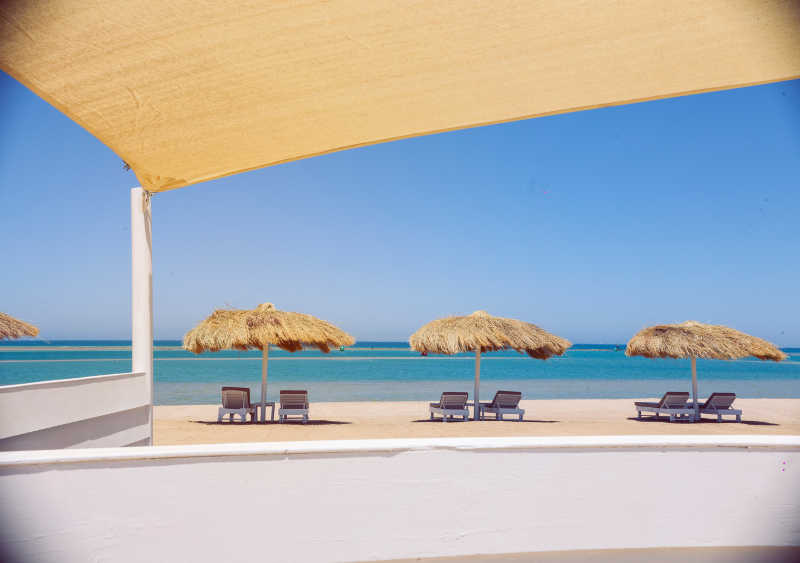Sunbeds and umberallas along the beach of Marina Beach Club in El Gouna with the blue rflection of Red Sea and clear sky