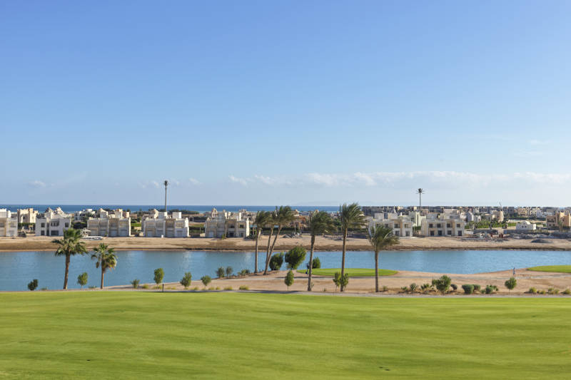 golf course with water pool and buildings at ancient sands golf resort el gouna
